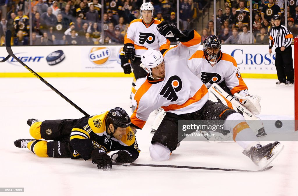 Gregory Campbell of the Boston Bruins and Nicklas Grossmann of the Philadelphia Flyers fall to the ice while battling for the puck during the game on...