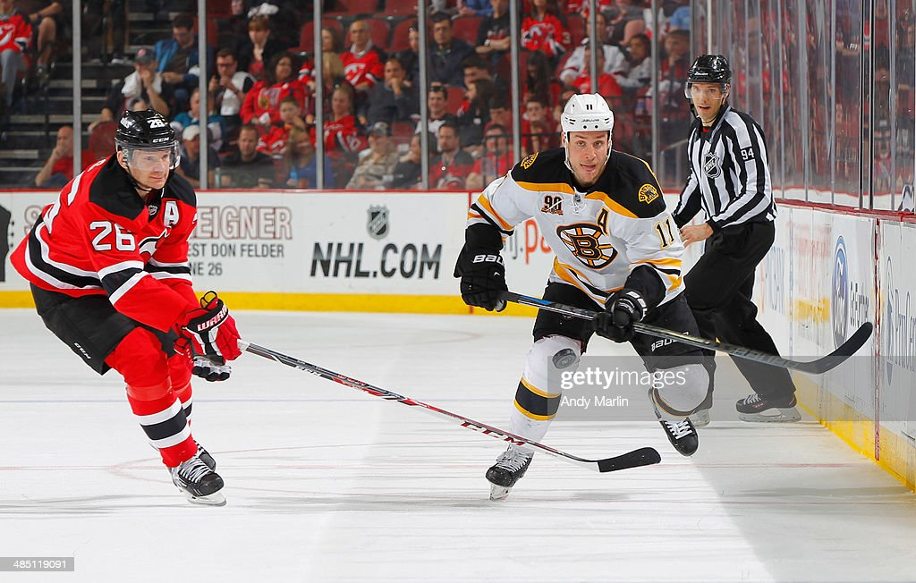 Gregory Campbell of the Boston Bruins and Patrik Elias of the New Jersey Devils pursue a loose puck during the game at the Prudential Center on April...