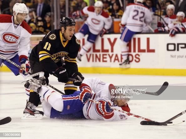 Gregory Campbell of the Boston Bruins helps bring down David Desharnais of the Montreal Canadiens at the TD Garden on December 19 2011 in Boston...