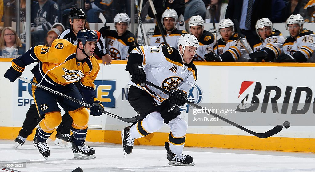 Gregory Campbell of the Boston Bruins skates against David Legwand of the Nashville Predators at Bridgestone Arena on December 23 2013 in Nashville...