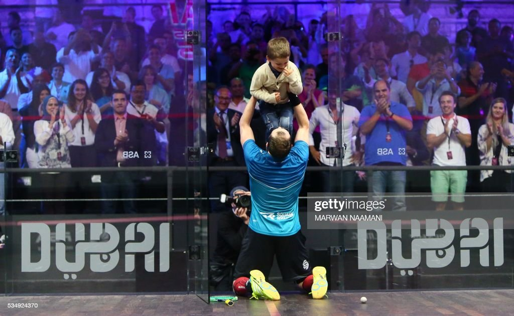 Gregory Gaultier of France celebrates with his son after beating Cameron Pilley (R) of Australia in the men's fianal match of the Dubai PSA World Series Finals squash tournament in Dubai, May 28, 2016. / AFP / MARWAN