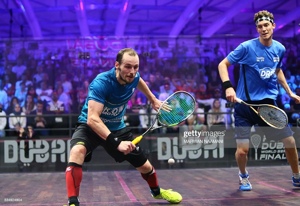 Gregory Gaultier (L) of France plays a backhand to Cameron Pilley of Australia in the men's final match of the Dubai PSA World Series Finals squash tournament in Dubai, on May 28, 2016. / AFP / MARWAN