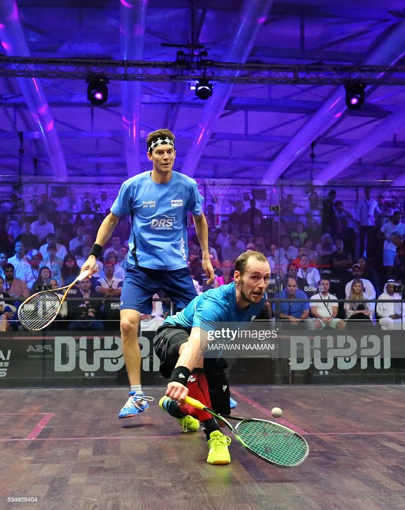 Gregory Gaultier (front) of France plays a backhand to Cameron Pilley of Australia in the men's final match of the Dubai PSA World Series Finals squash tournament in Dubai, May 28, 2016. / AFP / MARWAN