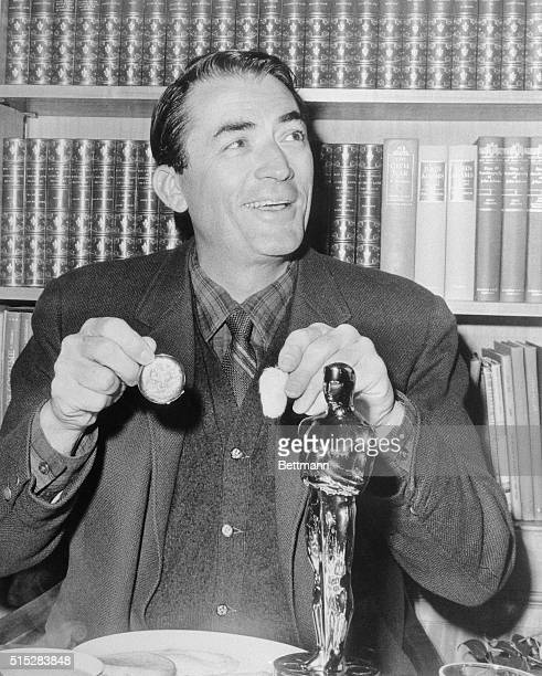 Gregory Peck has breakfast in the 'company' of his 'Oscar' April 9th Peck holds a rabbit's foot and a gold watch His daughter Cecilia gave him the...