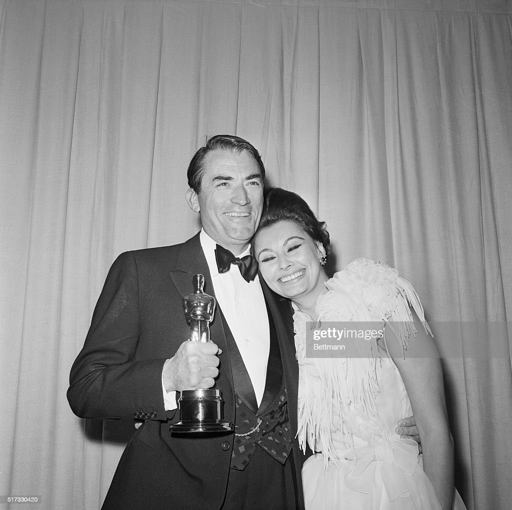 Gregory Peck holds his Academy Award for Best Actor (for To Kill A Mockingbird), while Sophia Loren puts her head on this shoulder. Loren had presented the Best Actor Oscar, as she had won for Best Actress the previous year. 1963.