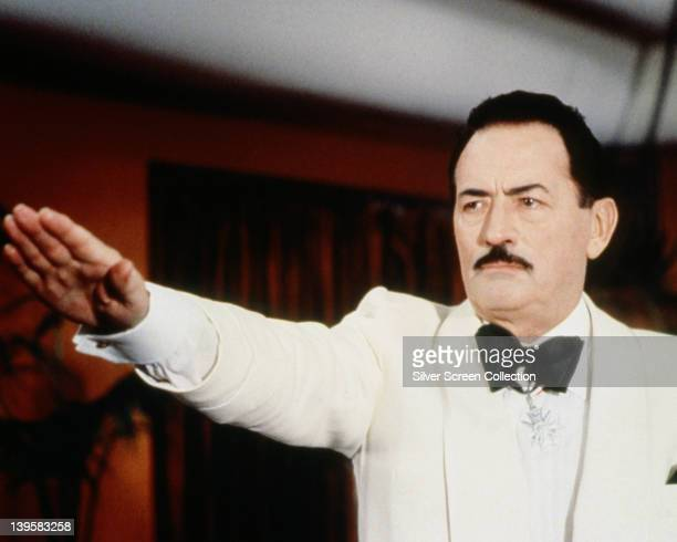 Gregory Peck US actor wearing a white jacket and white shirt with a black bow tie giving the Nazi salute with his right arm outstretched in a...