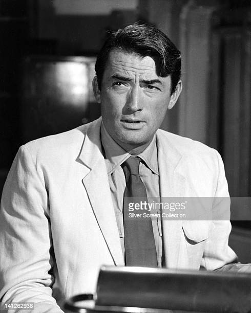 Gregory Peck US actor wearing a white jacket over a white shirt with a dark tie in a studio portrait against a dark background circa 1965