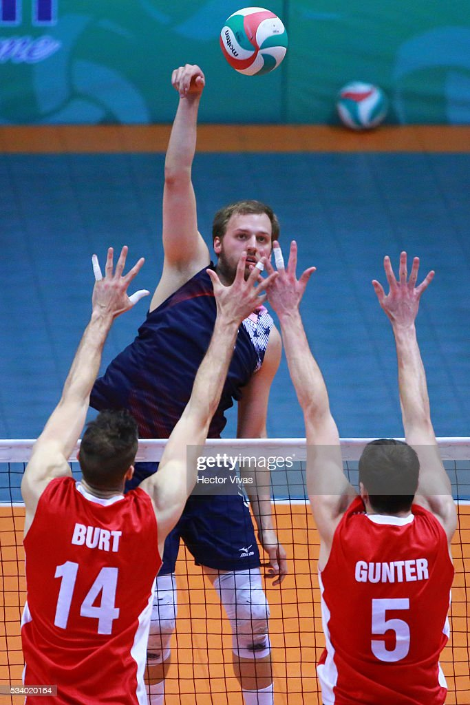 Gregory Petty of United States spikes the ball against Max Burt and Robert Gunter of Canada during a match between USA and Canada as part of Men's Panamerican Volleybal Cup at Gimnasio Ol'mpico Juan de la Barrera on May 24, 2016 in Mexico City, Mexico.