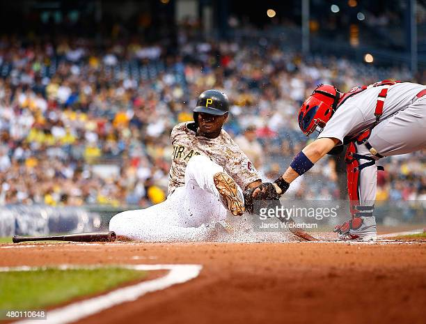 Gregory Polanco of the Pittsburgh Pirates is tagged out at home plate by Yadier Molina of the St Louis Cardinals in the first inning during the game...