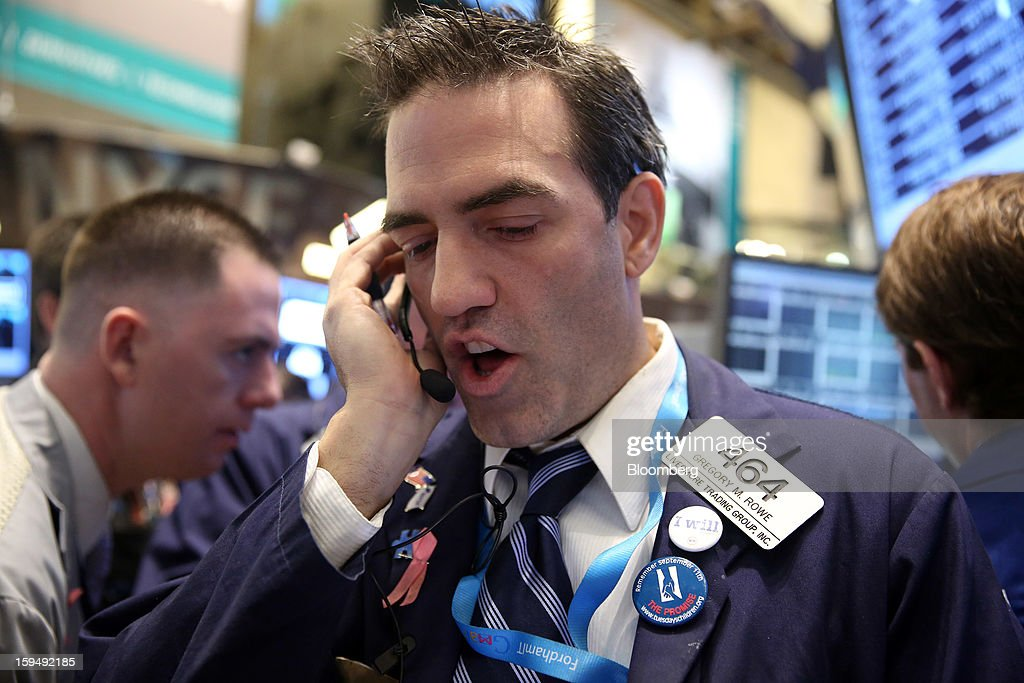 Gregory Rowe, a trader with Livermore Trading Group Inc., works at the New York Stock Exchange (NYSE) in New York, U.S., on Monday, Jan. 14, 2013. U.S. stocks fell, after the Standard & Poor's 500 Index climbed for two weeks to trade near the highest level in five years, as Apple Inc. tumbled amid a report it cut orders for iPhone components. Photographer: Scott Eells/Bloomberg via Getty Images