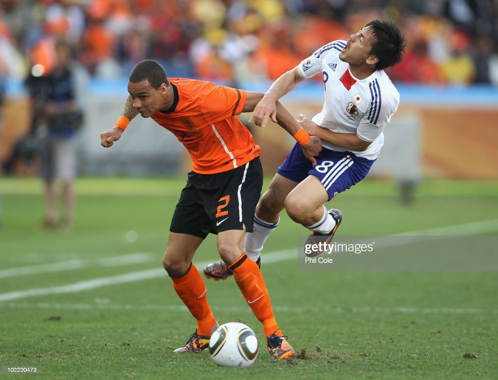 Gregory Van Der Wiel of the Netherlands clashes with Daisuke Matsui of Japan during the 2010 FIFA World Cup South Africa Group E match between Netherlands and Japan at Durban Stadium on June 19, 2010 in Durban, South Africa.
