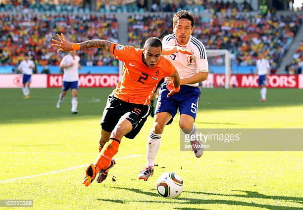 Gregory Van Der Wiel of the Netherlands is challenged by Yuto Nagatomo of Japan during the 2010 FIFA World Cup South Africa Group E match between...