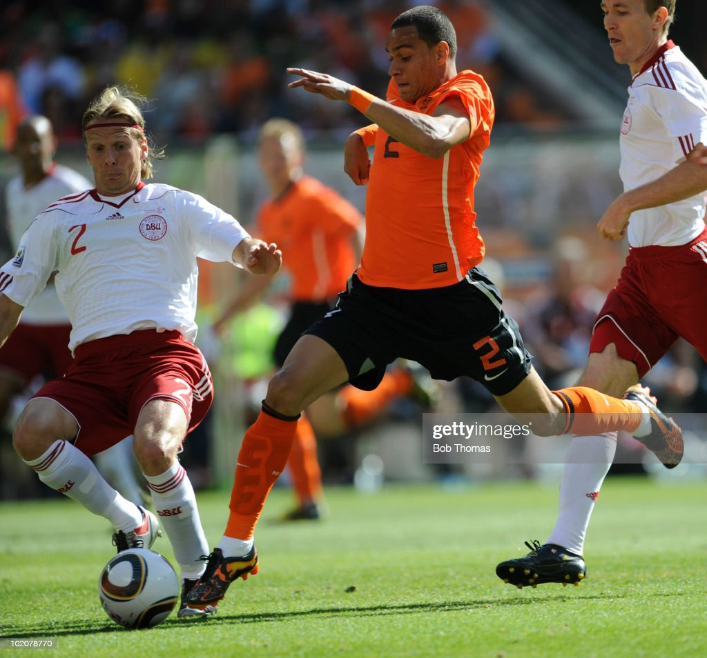 Gregory Van der Wiel of the Netherlands tackled by <a gi-track='captionPersonalityLinkClicked' href=/galleries/search?phrase=Christian+Poulsen&family=editorial&specificpeople=228068 ng-click='$event.stopPropagation()'>Christian Poulsen</a> of Denmark during the 2010 FIFA World Cup Group E match between Netherlands and Denmark at Soccer City Stadium on June 14, 2010 in Johannesburg, South Africa.