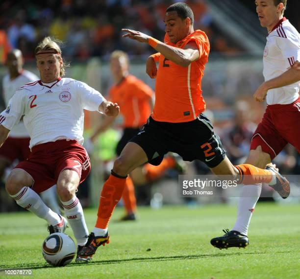Gregory Van der Wiel of the Netherlands tackled by Christian Poulsen of Denmark during the 2010 FIFA World Cup Group E match between Netherlands and...