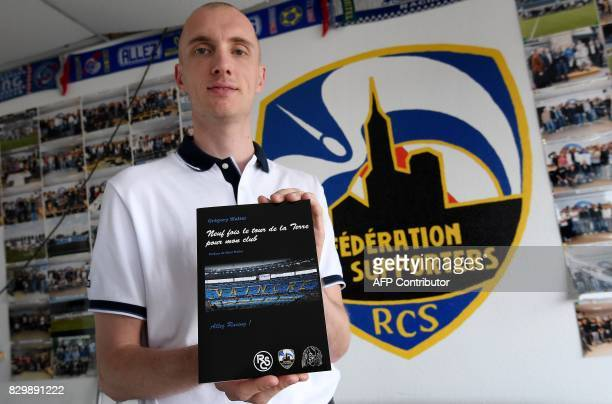 Gregory Walter a supporter of the Racing Club of Strasbourg football team holds a book reading 'Nine times the world tour for my club' as he poses on...