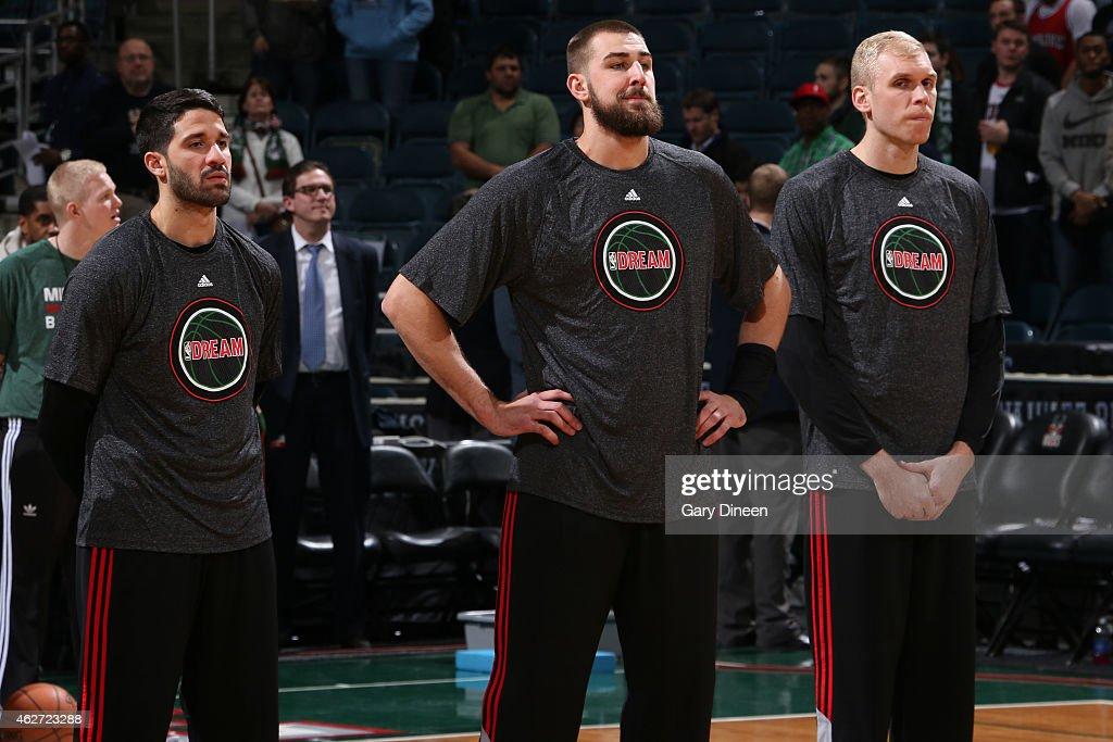 Greivis Vasquez Jonas Valanciunas and Greg Stiemsma of the Toronto Raptors stand for the national anthem before a game against the Milwaukee Bucks on...