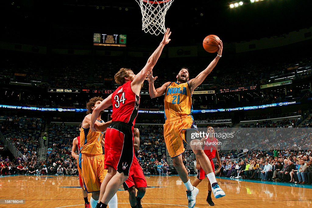 Greivis Vasquez #21 of the New Orleans Hornets drives to the basket against Aaron Gray #34 of the Toronto Raptors on December 28, 2012 at the New Orleans Arena in New Orleans, Louisiana.