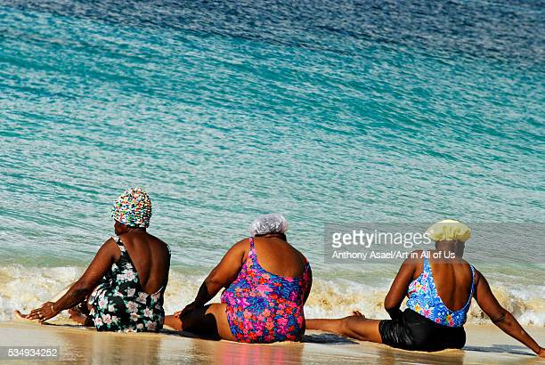 Grenada St George three mid adult chunky women sitting on the beach with old style bathing suit