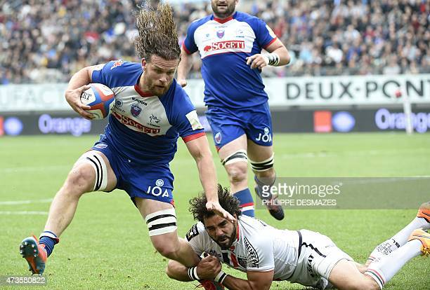 Grenoble's French flanker Fabien Alexandre is tackled by Toulouse's French winger Yoann Huget during the French Top 14 rugby union match between...
