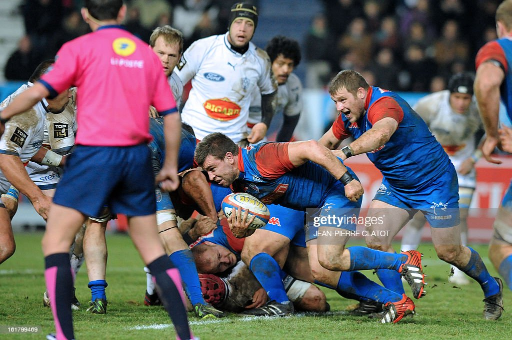 Grenoble's French hooker Vincent Campo (C) runs with the ball during the French Top 14 rugby union match Grenoble (FCG) vs Agen (SU) on Ffebruary 16, 2013 at the Stade Lesdiguieres in Grenoble. AFP PHOTO / Jean Pierre Clatot