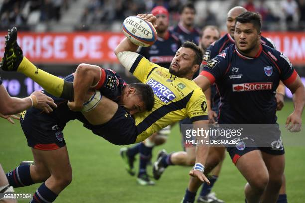 Grenoble's French lock Mathias Marie tackles Clermont's French flanker Damien Chouly during the French Top 14 rugby union match between FCG Grenoble...