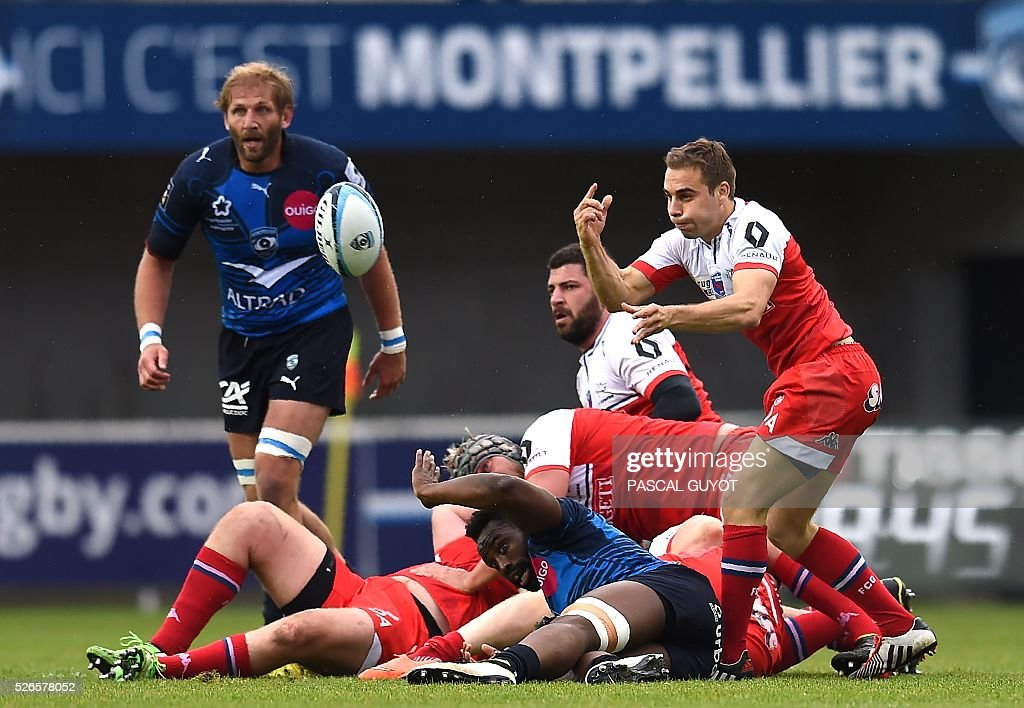 Grenoble's French scrumhalf James Hart (R) passes the ball during the French Top 14 rugby union match between Montpellier and Grenoble on April 30, 2016 at the Altrad stadium in Montpellier, southern France.