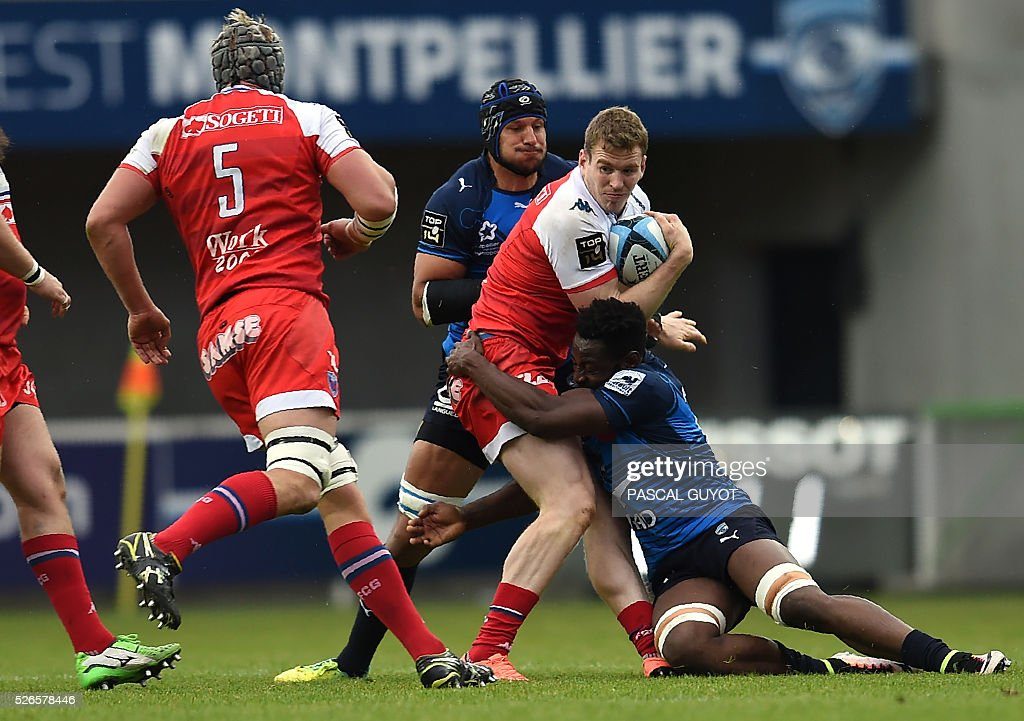 Grenoble's Irish centre Chris Farrell (C) vies with Montpellier's French flanker Fulgence Ouedraogo (R) during the French Top 14 rugby union match between Montpellier and Grenoble on April 30, 2016 at the Altrad stadium in Montpellier, southern France.