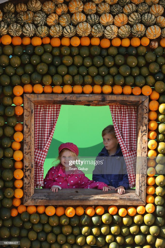 Greta, 4, and her sister Nele, 7, look out from the window of an alpine hut decorated entirely with pumpkins and squash at the Spargelhof Buschmann & Winkelmann farm on October 1, 2013 in Klaistow, Germany. The Buschmann & Winkelmann farm, which grows approximately 80 different kinds of pumkins and squash, hosts an annual amusement park with tens of thousands of pumpkins and squash arranged into decorations that this year are under a Heidi and the Alm alpine theme.