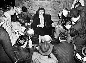 Greta Garbo with photographers swarming around her in a lounge on the 'Gripsholm' ocean liner which was bringing her back to the United States after...