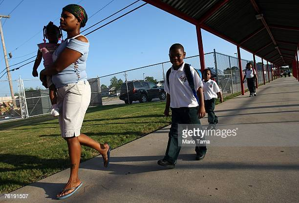 Gretchen Castor carries daughter Jani as sons Jordan and Jaylen follow on the first day of school for kindergartners at Dr Martin Luther King Jr...