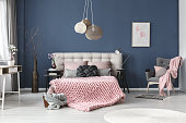 Grey armchair with pink blanket and pastel pillow in bedroom with subtle painting on blue wall