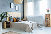 Grey bedroom with crate furniture, double bed and plants