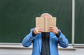 grey hair professor covering face with book