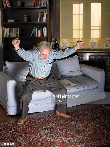 Grey haired man leaping off sofa in front of television. Alicante, Spain.