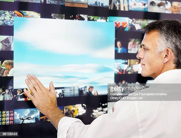 grey haired man using a digital display