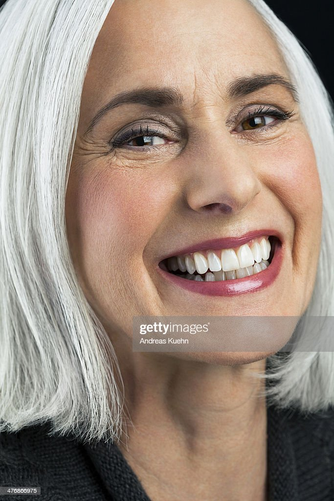 Grey haired mature woman laughing, close up.