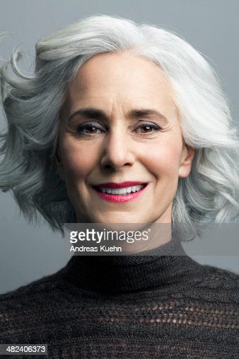 Grey haired mature woman smiling, portrait.