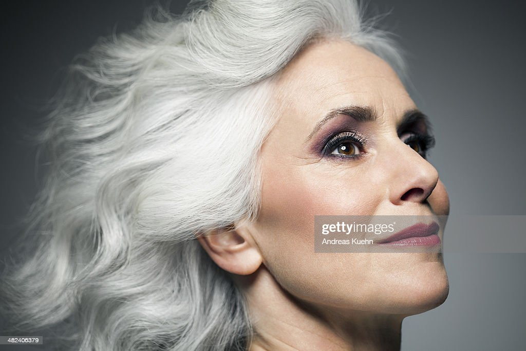 Grey haired woman in profile position, portrait.
