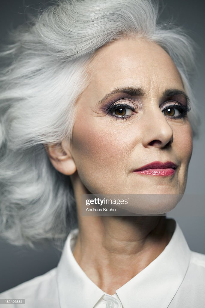 Grey haired woman in white shirt, portrait.