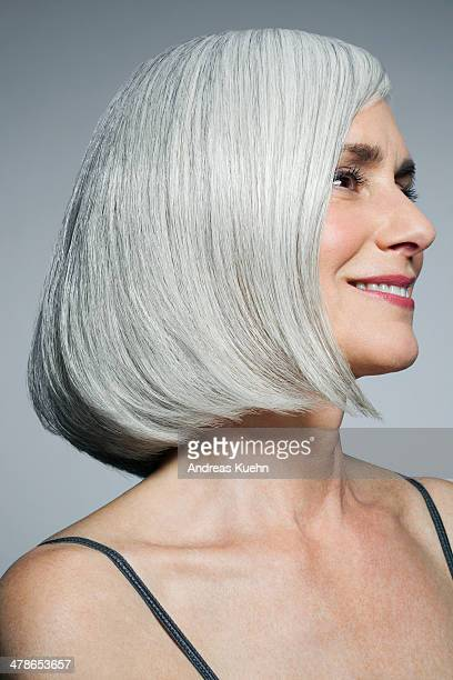 Grey haired woman looking off camera, smiling.