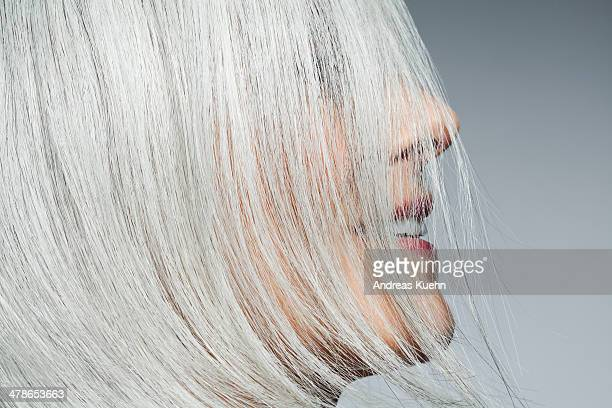 Grey haired woman profile with hair covering face.