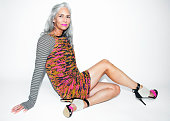 Grey haired woman wearing a funky outfit.
