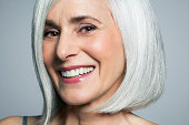 Grey haired woman with a big smile, close up.