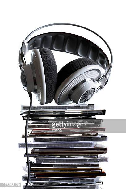 A grey headphone on top of a stack of CD cases