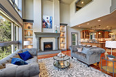 Grey interior of high vaulted ceiling family room in luxury house. Northwest, USA.