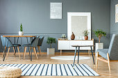 Pouf on striped carpet in grey interior with paintings, chair at dining table and bonsai next to white cupboard