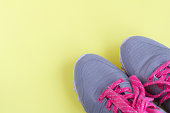 grey sneakers with pink laces on light yellow background