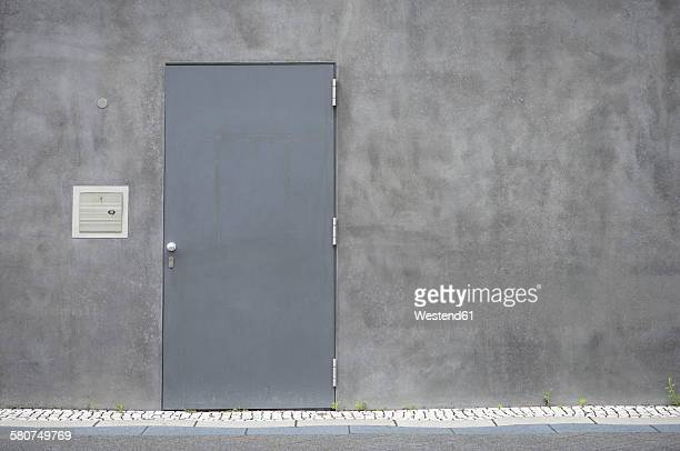 Grey steel door at concrete wall