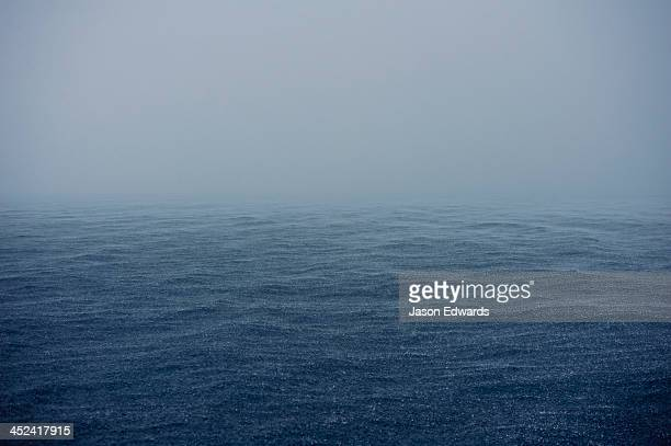 A grey torrential downpour lashes the surface of a tropical ocean.