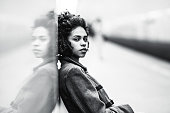 Black and white portrait of charming African American female in the coat leaning against a mirror wall; the greyscale shot of a cute black teenage girl sitting on the bench of an underground station